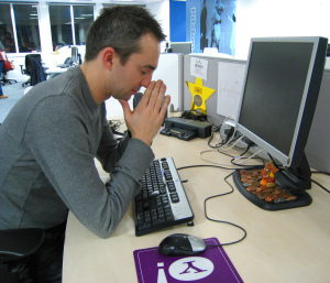 Man praying at computer
