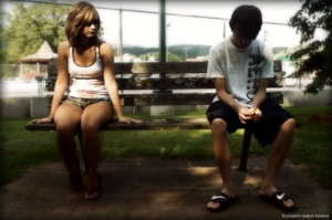 Young_couple_sitting_apart_on_park_bench